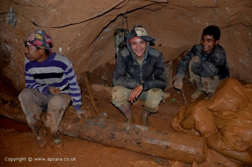 Miners in the mine next to sacks of soil